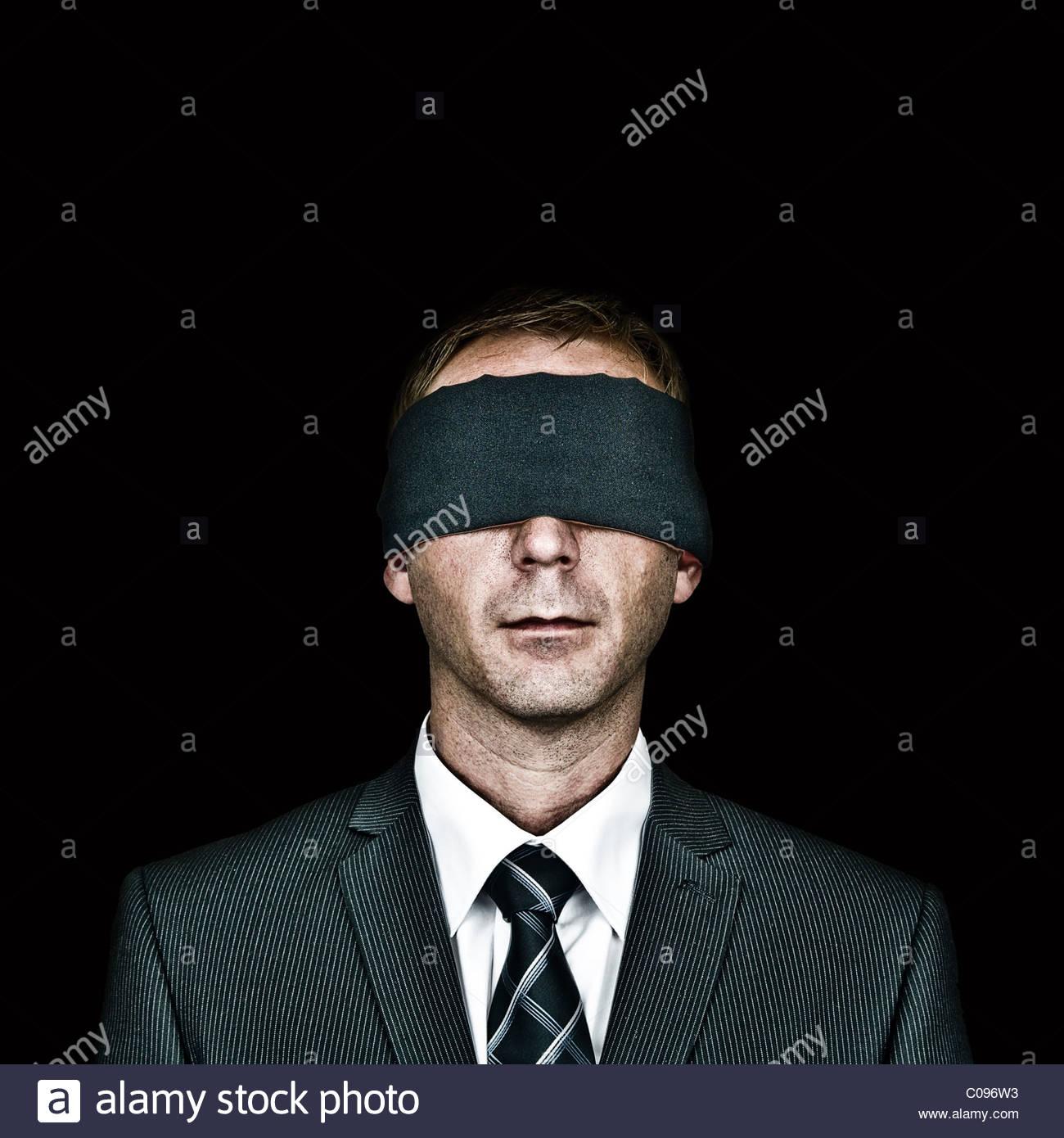 Man blindfolded on black background - Stock Image