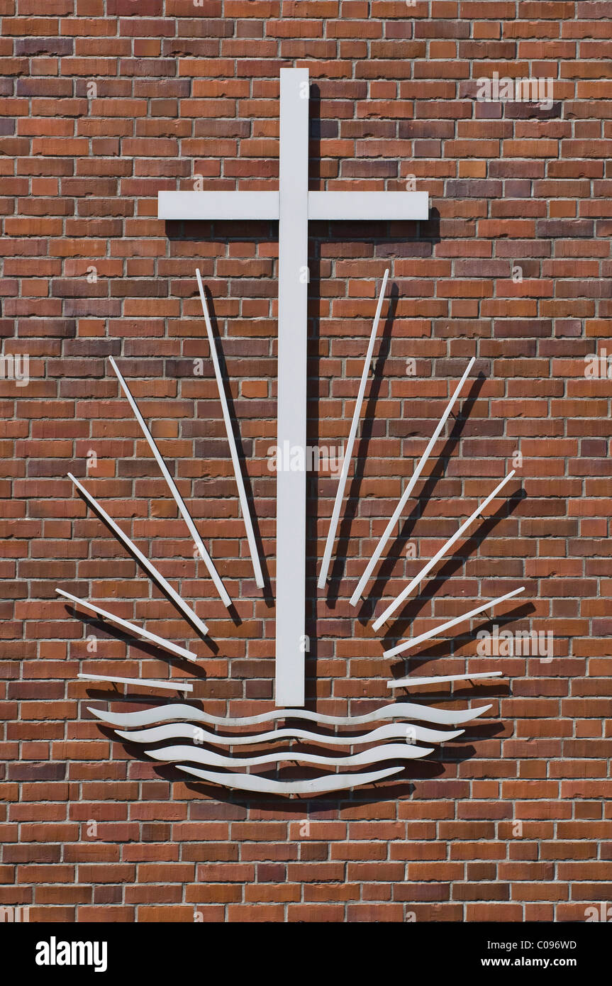 Cross over the rising sun and water waves, emblem of the New Apostolic Church on a brick wall - Stock Image