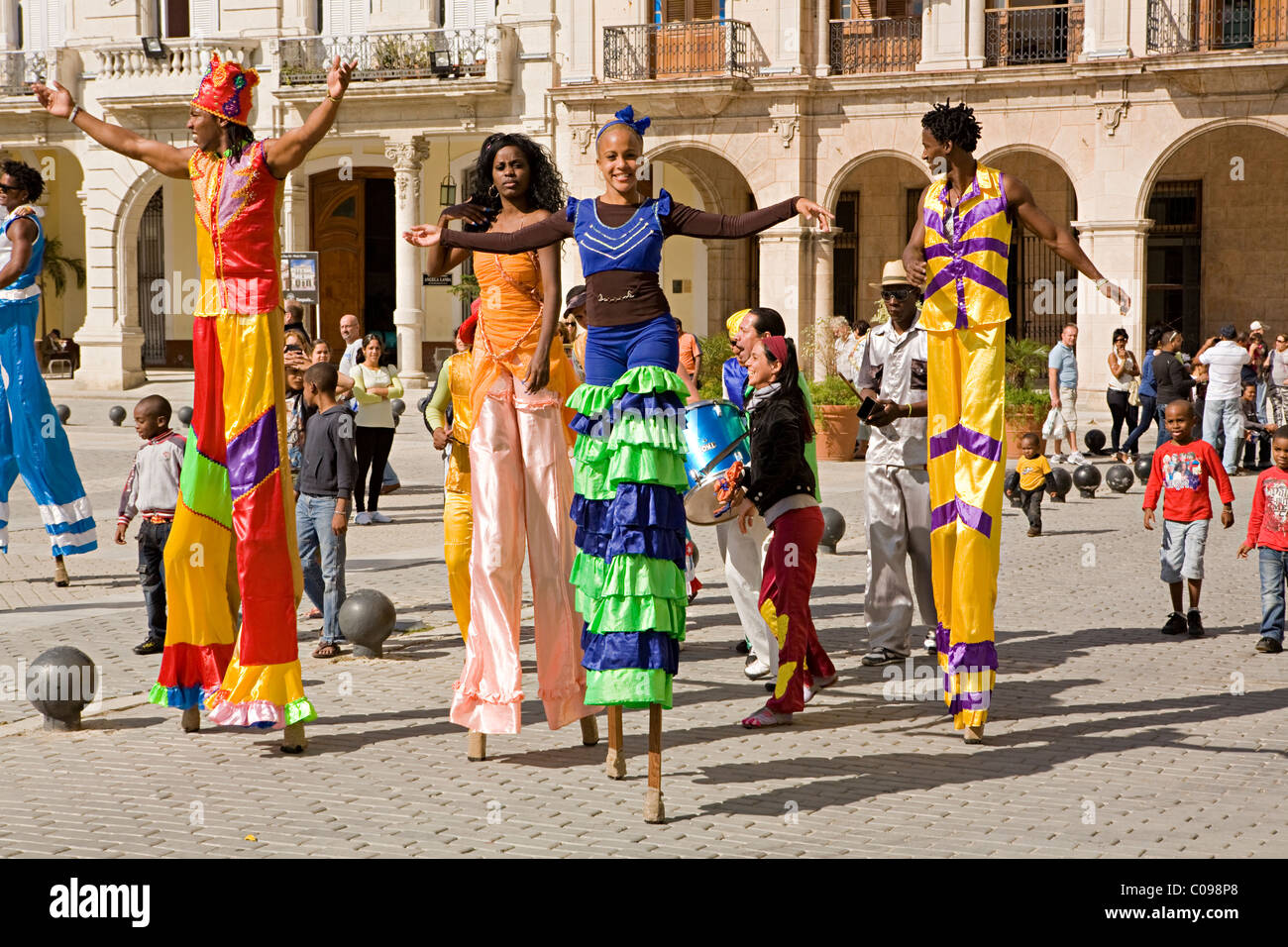 A group of street artist or performers parading on stilts walk through the streets of Havana, Cuba in bright colourful - Stock Image
