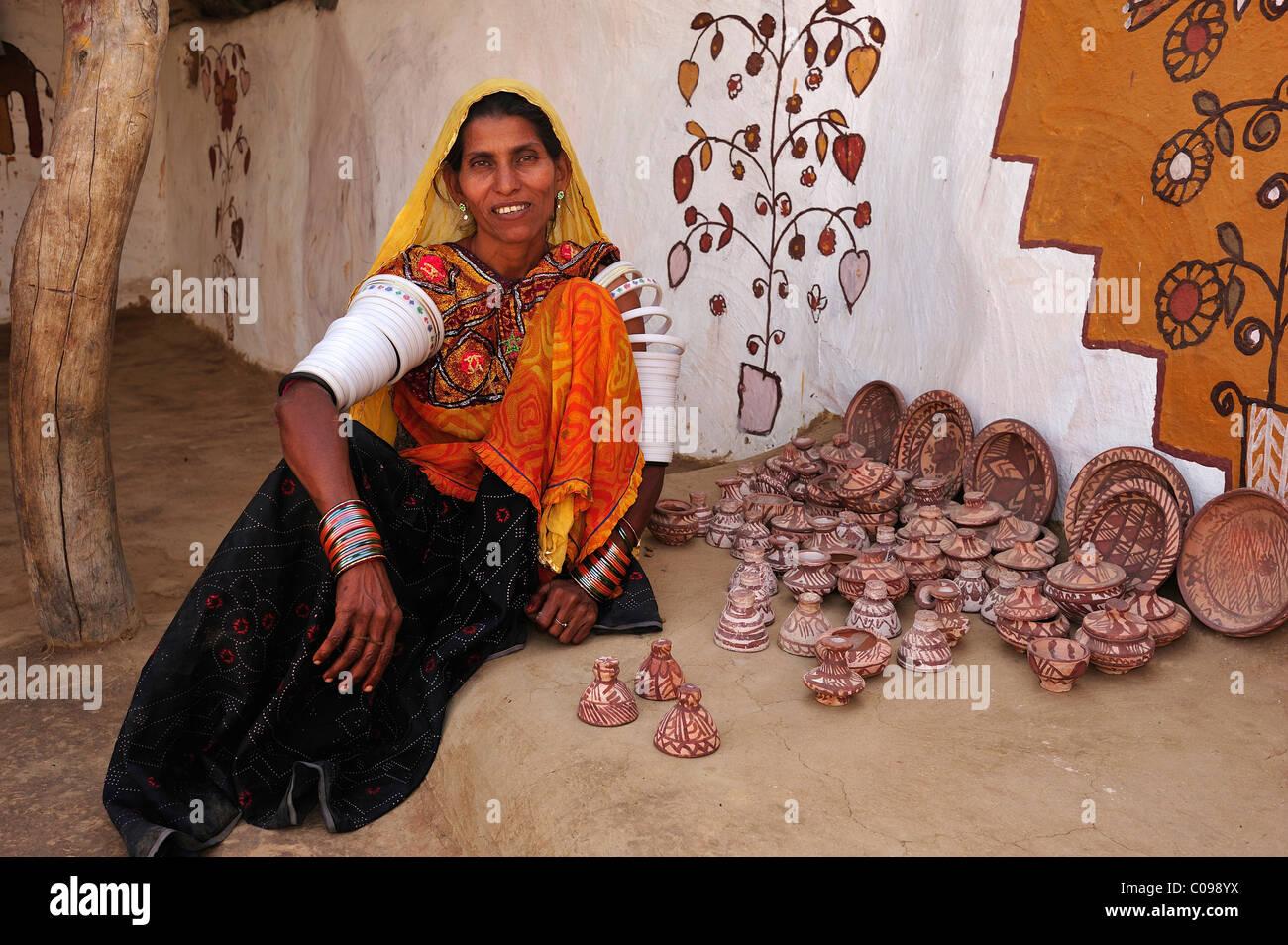 Female potter sitting next to a selection of ceramics in front of a traditional house, Thar Desert, Rajasthan, India, - Stock Image