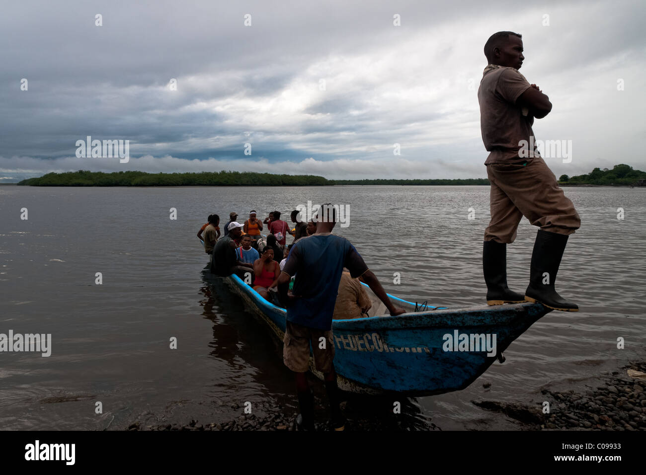 Colombian shellfish pickers embark on a canoe going to the mangrove swamps on the Pacific coast, Colombia. - Stock Image