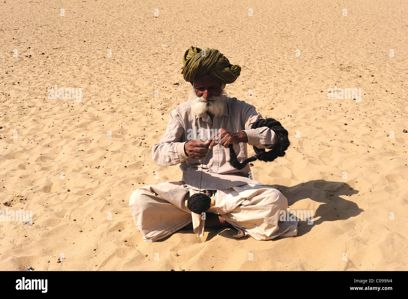 Old man spinning wool with a hand spindle, Thar Desert, Rajasthan, North India, India, Asia - Stock Image
