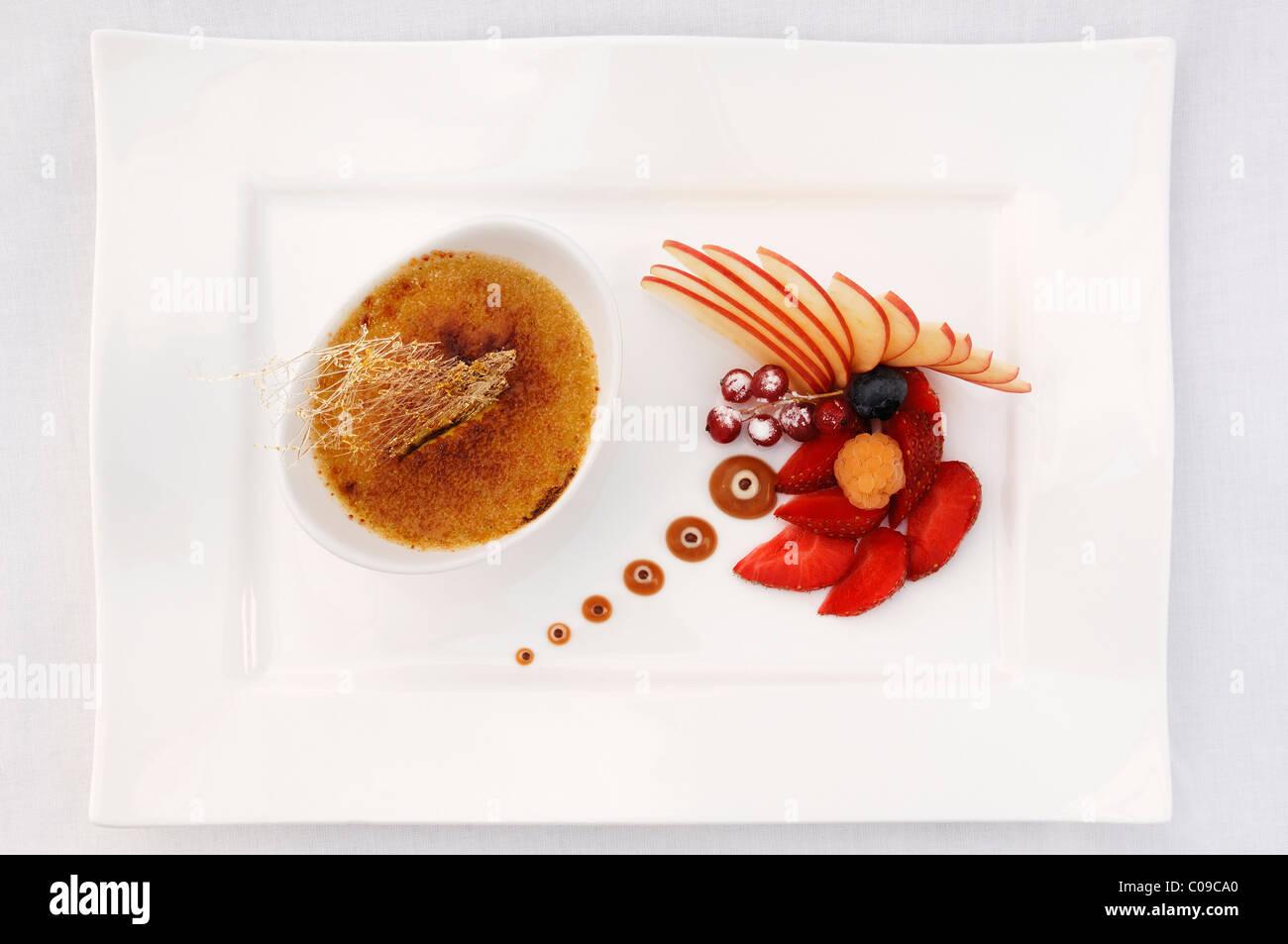 Dessert, tonka bean crème brûlée decorated with fruit, Haute Cuisine, Auberge de la Ferme Hueb, Mike - Stock Image