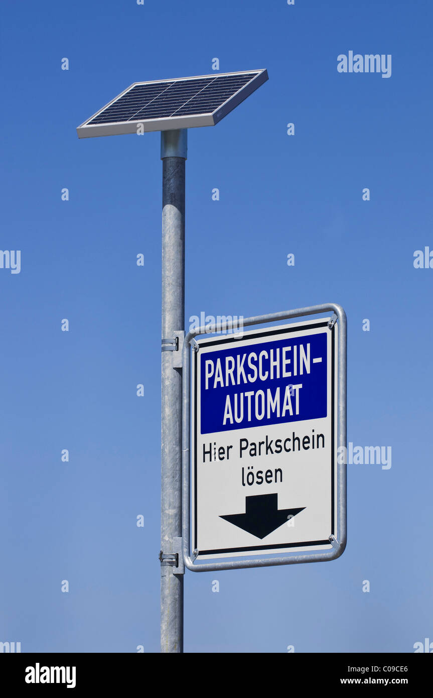 Solar panels of a parking meter with a sign on a pole - Stock Image