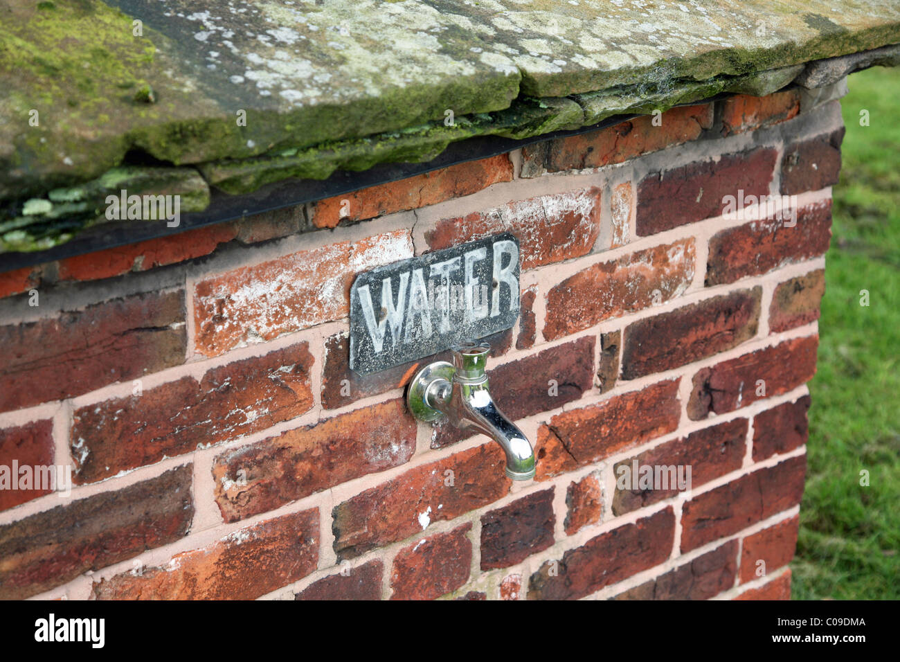 An outdoor water tap with a sign saying water on a brick wall - Stock Image