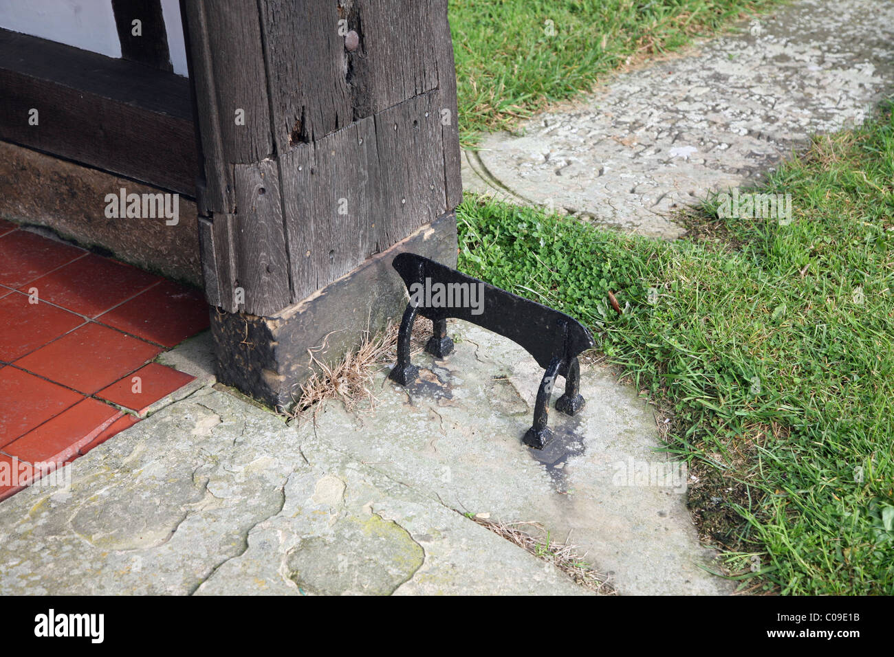 a metal iron foot scraper outside a wooden church porch - Stock Image