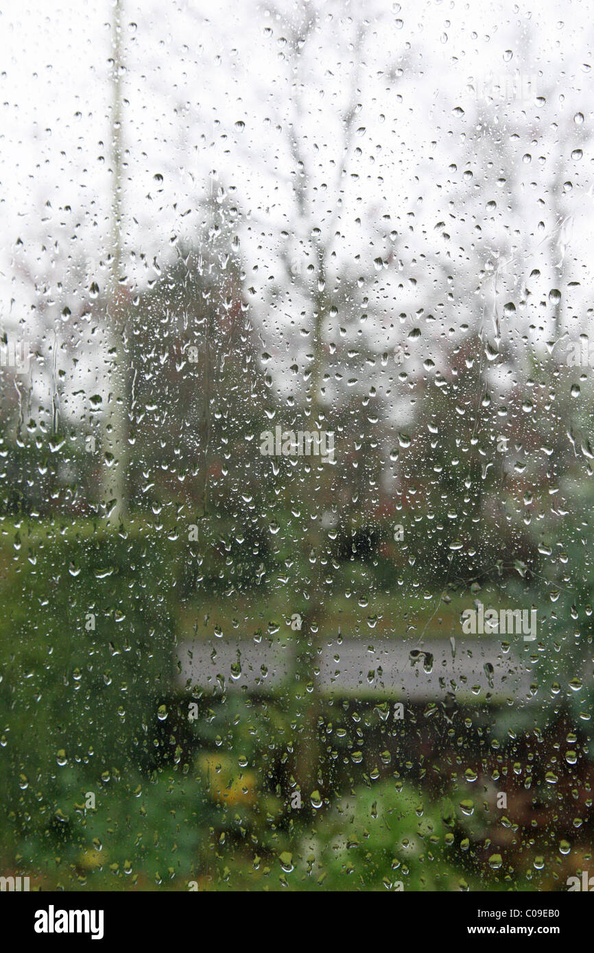 A view out of a rain covered window with rain drops on the window - Stock Image