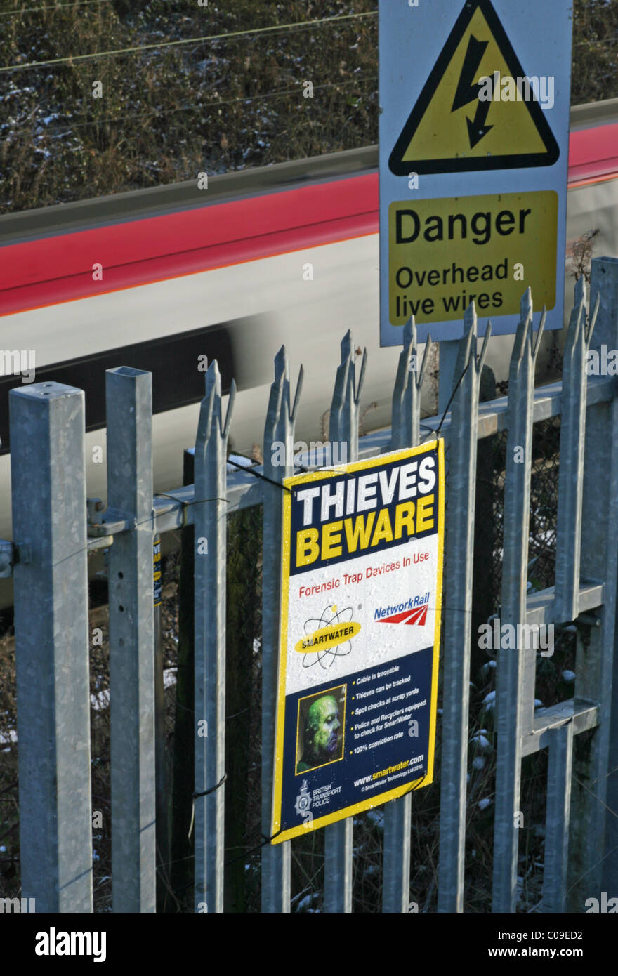 a sign next to a railway line saying thieves beware because of Smartwater - Stock Image