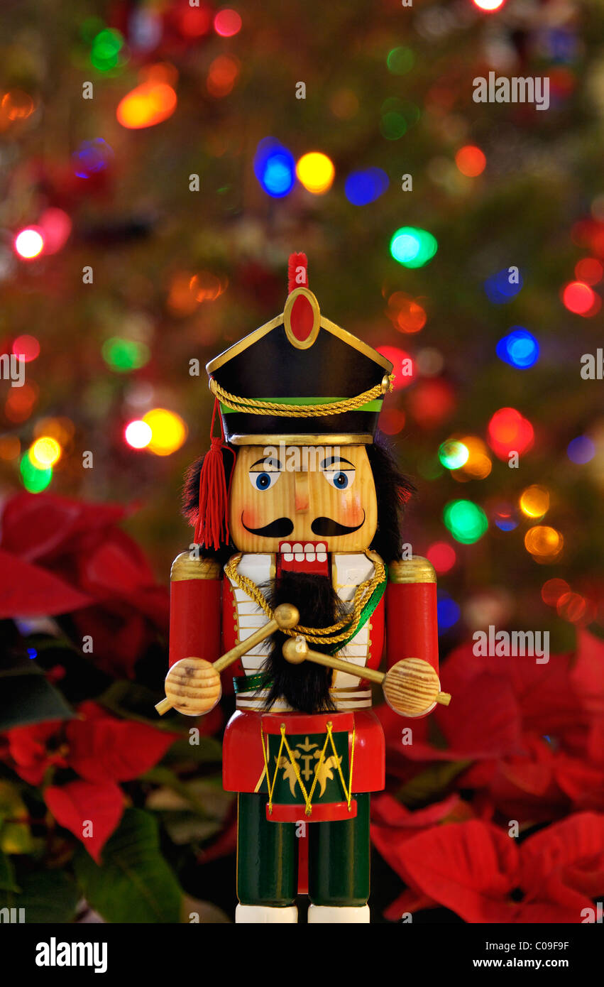 Nutcracker with Background of Poinsettia and Christmas Tree - Stock Image