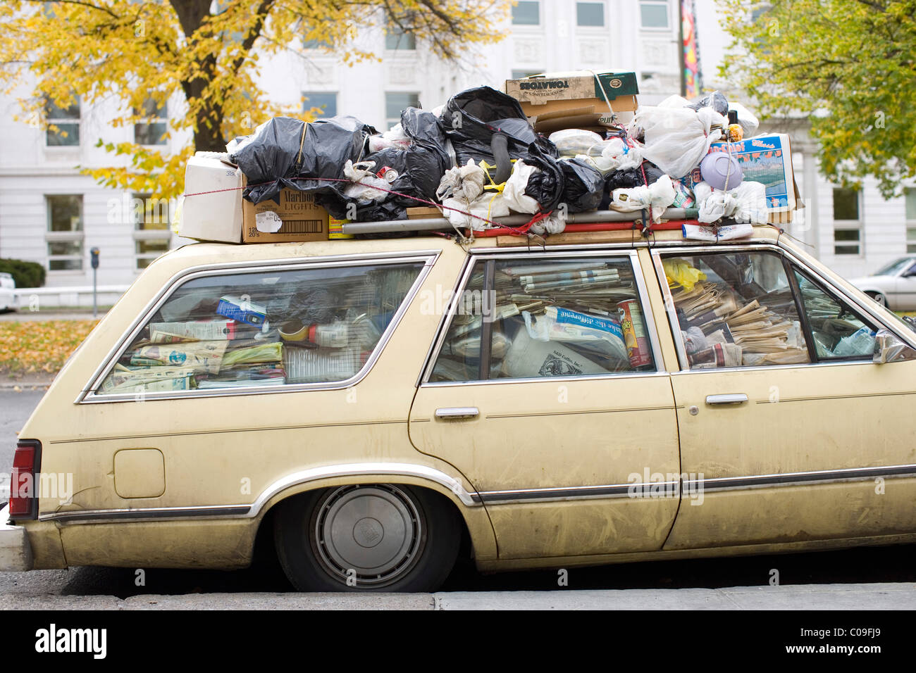 A parked car filled with garbage and recyclable material - Stock Image