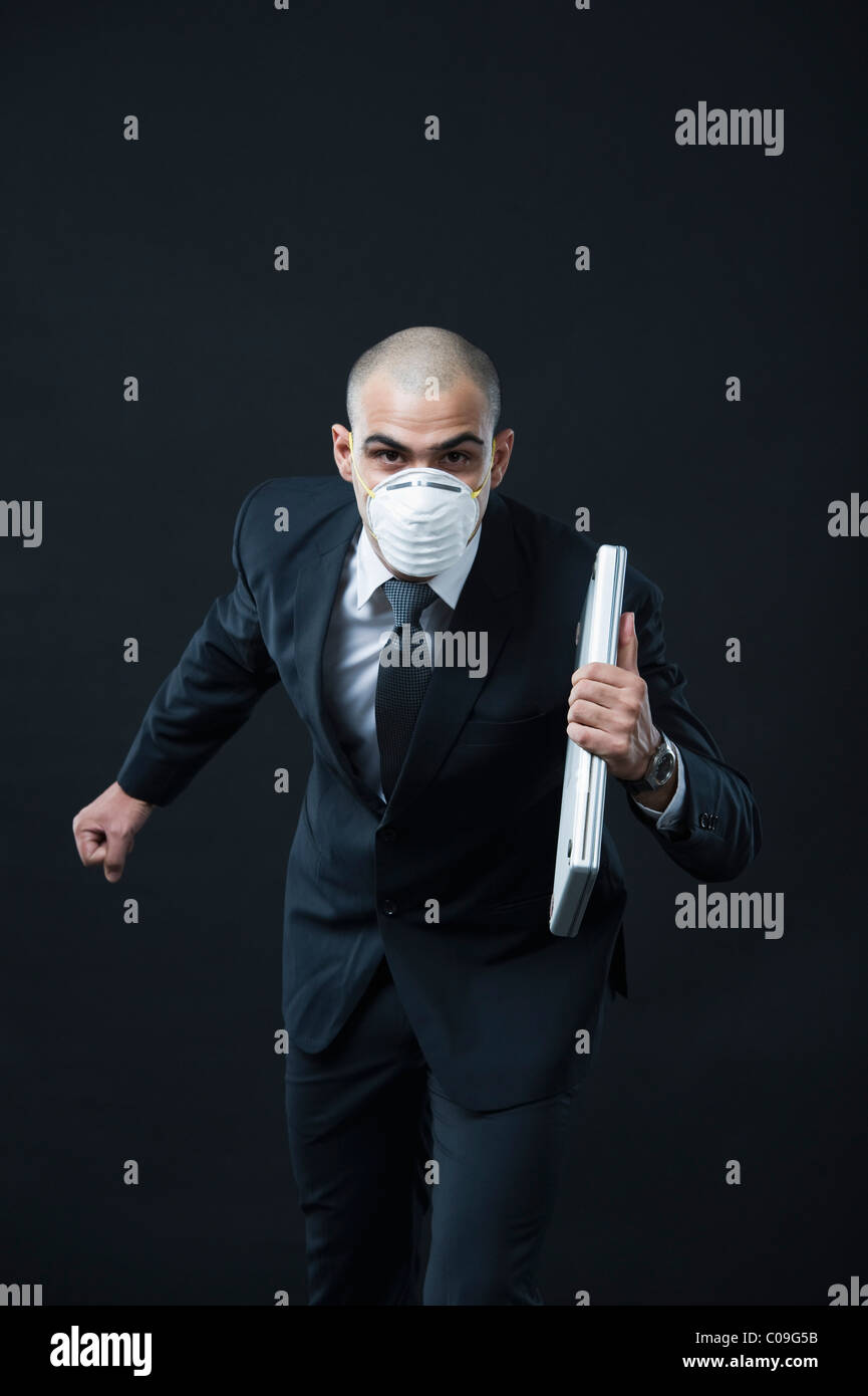 Portrait of a businessman wearing a pollution mask and running - Stock Image