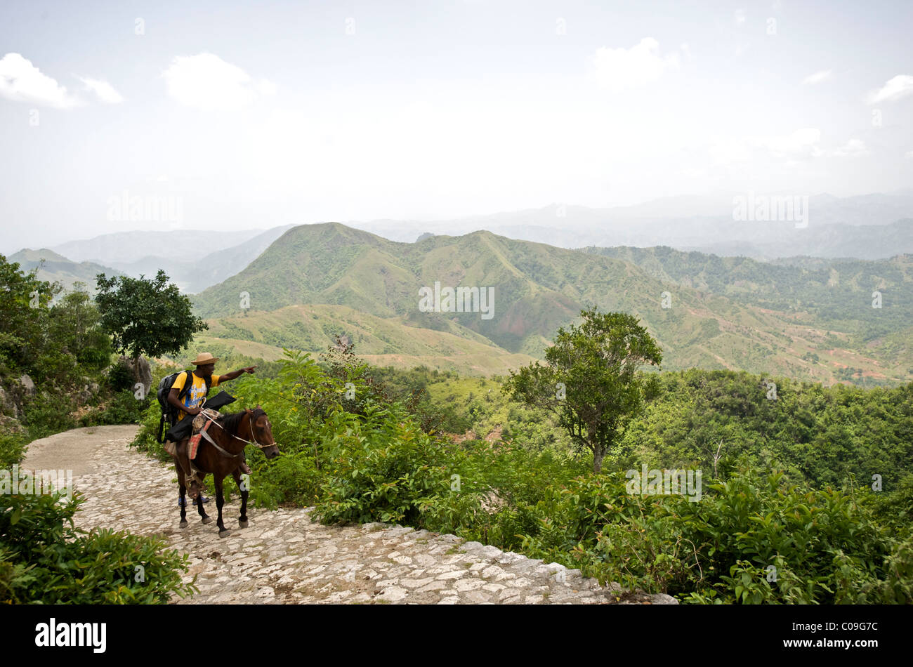A man ascends a miles long road on horseback while making his way to the Citadel in northern Haiti. Stock Photo