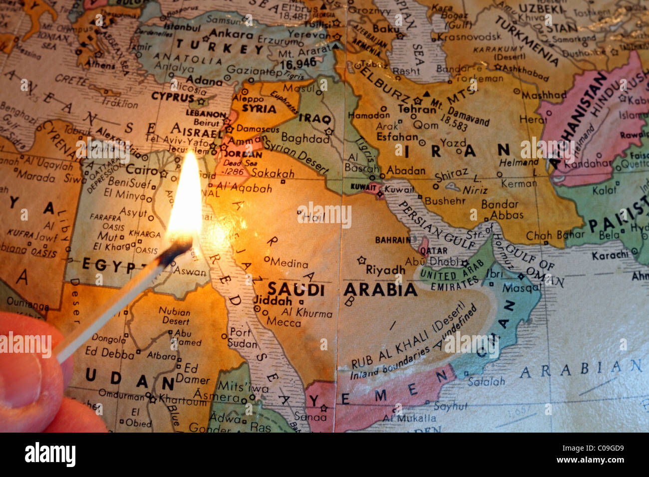 Middle East map with a lit match symbolizing the region's unrest with respect to social, religious and political - Stock Image