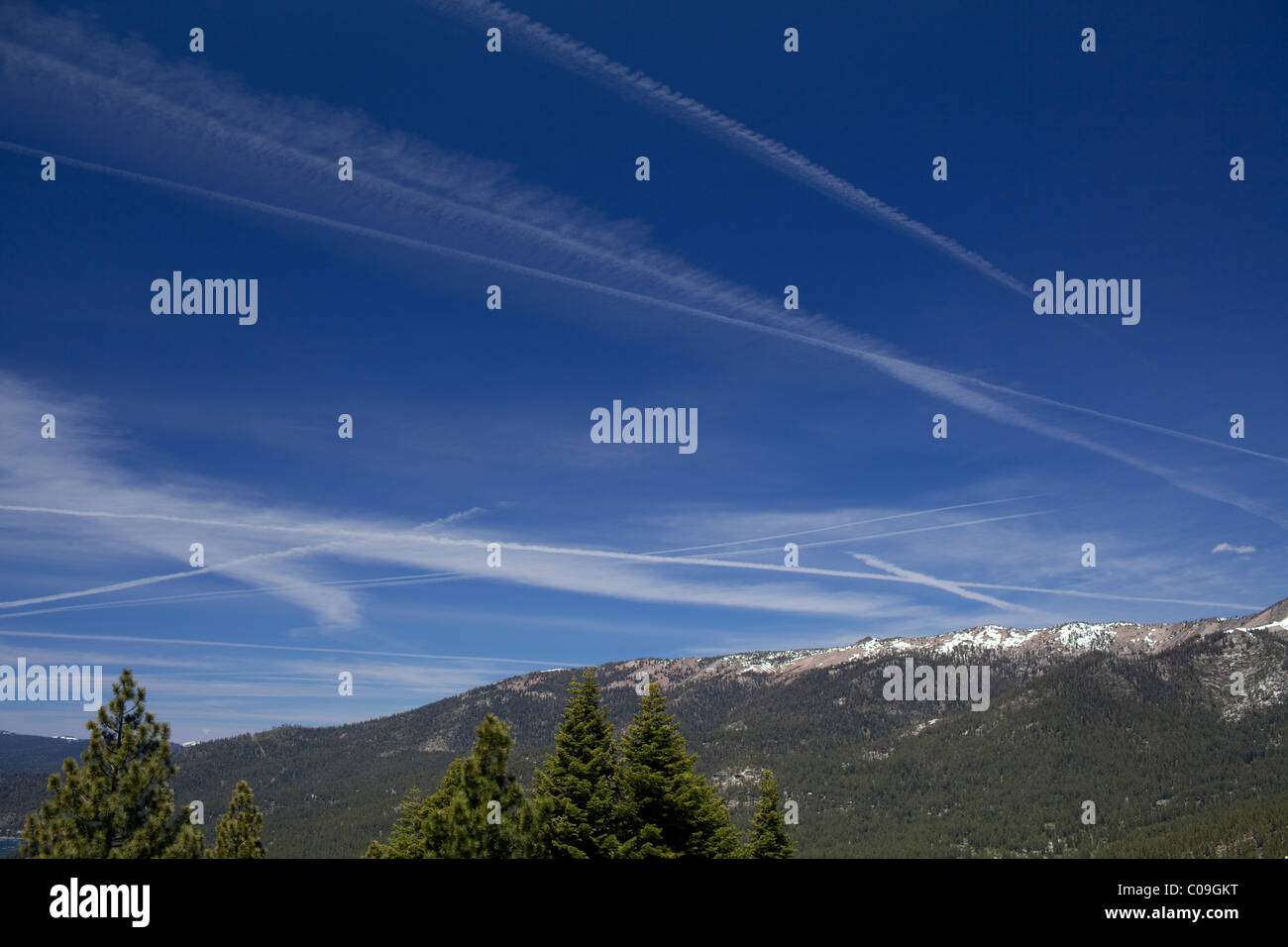 Vapor trails from high-flying jet airplanes in blue sky above Lake Tahoe on the border between California and Nevada - Stock Image