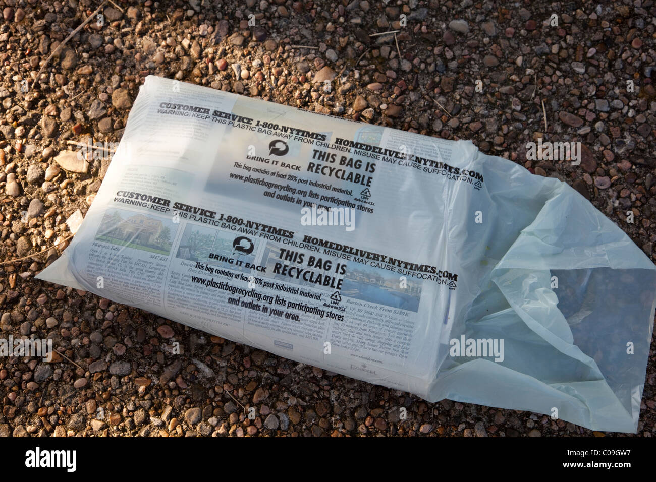 Home-delivered copy of daily newspaper wrapped in recyclable plastic bag rests on driveway of residence in Austin - Stock Image