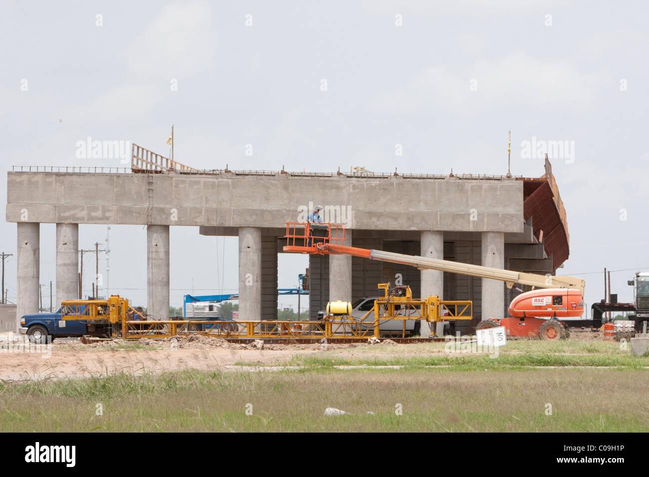 Hard-hat worker stands in basket of boom lift during bridge Stock