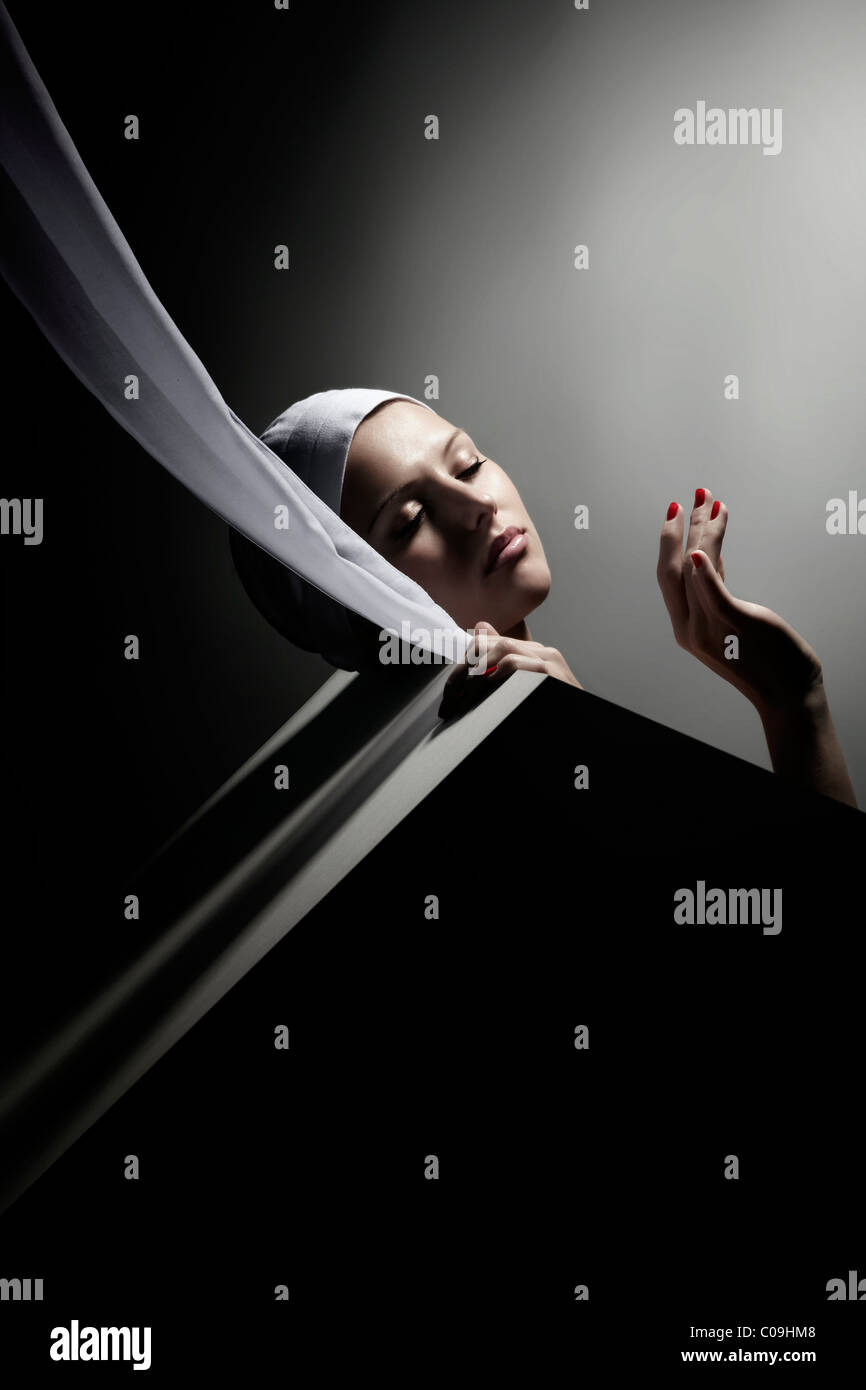 Young woman in a white cap, her head placed on a slanted wall and her hand gracefully held up - Stock Image