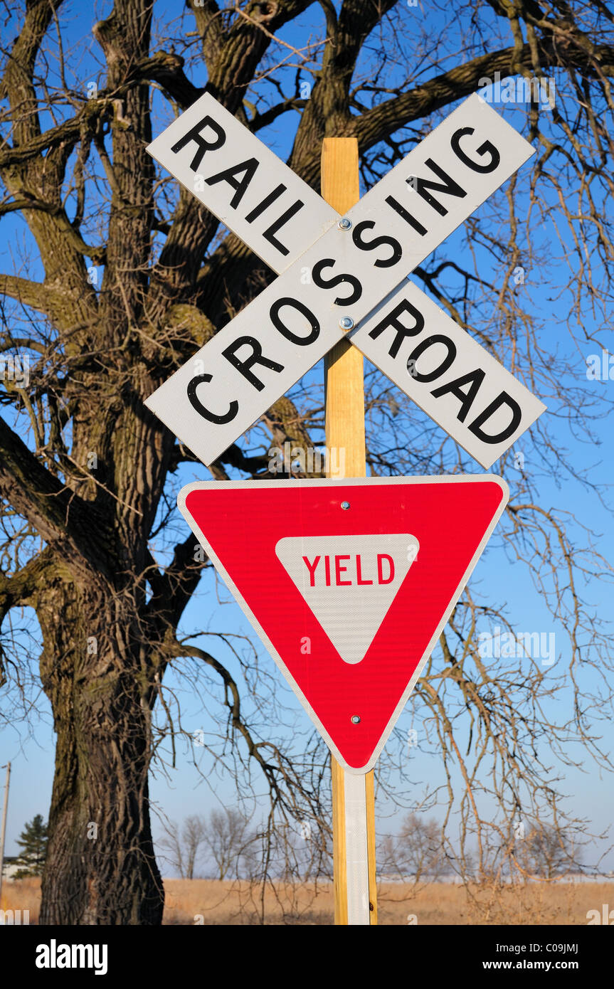 A rural railroad crossing marked only with road signs sit in front of a gnarled old tree in agriculture country - Stock Image
