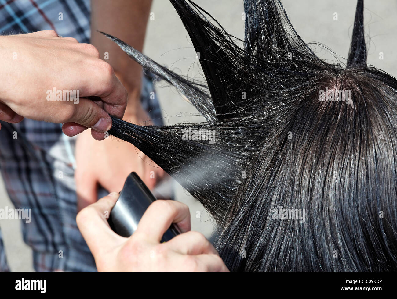 Hands spraying and styling hair shaped into tips of a teenager, hairstyle with spikes like a cockscomb, mohawk, - Stock Image