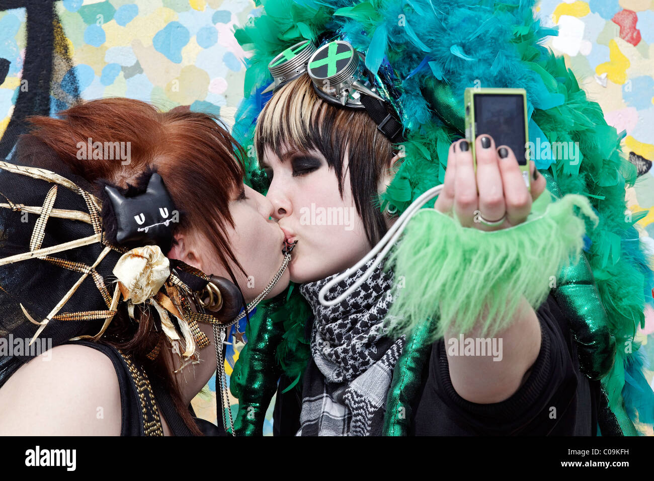Two young women with bizarre headdress kissing and photographing themselves with their mobile phone, imaginative - Stock Image