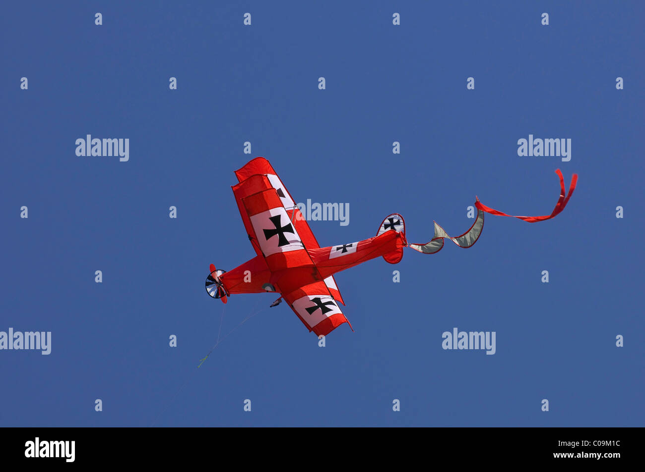 Red double-decker as a kite in flight - Stock Image
