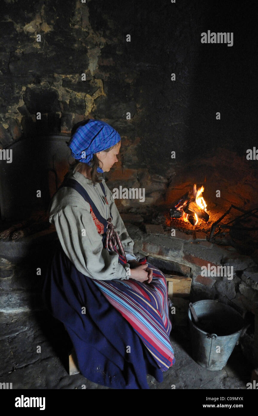 Woman at old stove in a museum, Oestarp, Skåne, Sweden, Europe Stock Photo