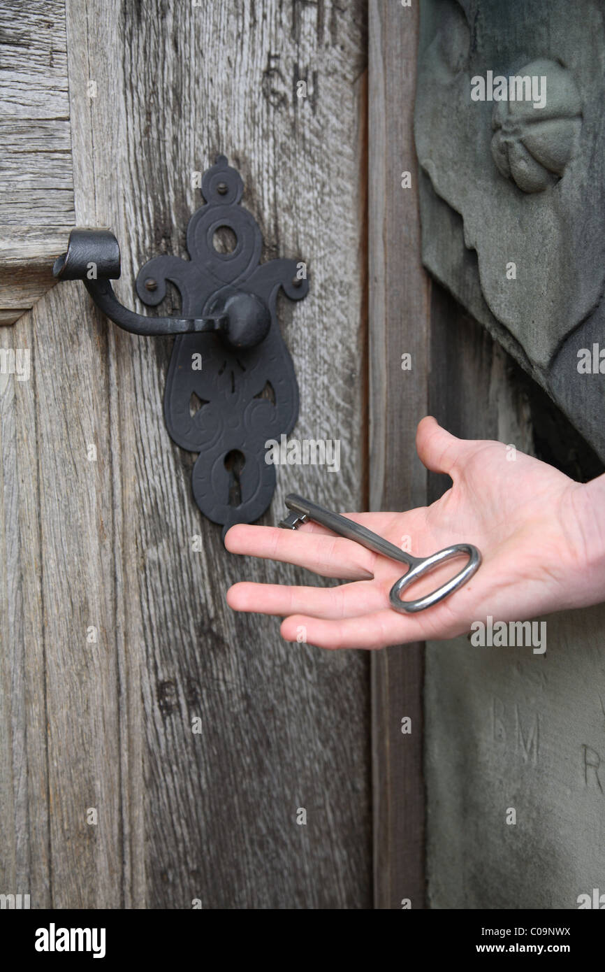 Key lying in open palm of a hand ready to open an old solid oak castle door to  renaissance castle Kronborg with - Stock Image