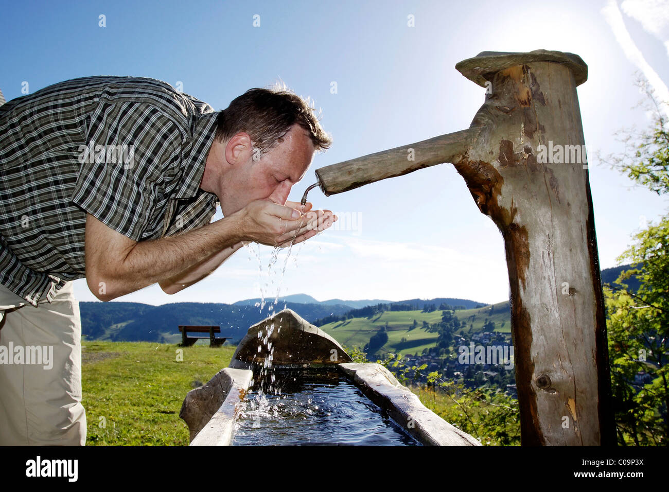 A man in his mid 40 quenches his thirst at a well, Todtnauberg in the Black Forest, Baden-Wuerttemberg, Germany, Stock Photo