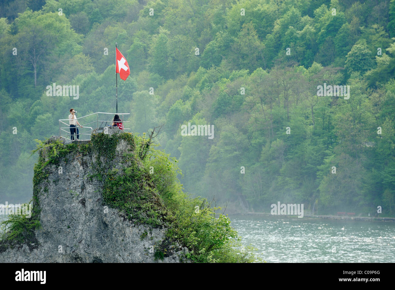 Viewpoint rock with tourists and the Swiss flag near the Rhine Falls, Schaffhausen, Switzerland, Europe - Stock Image