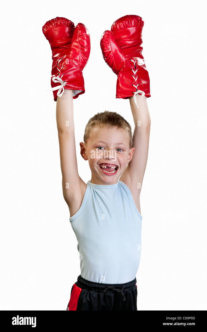 A boy, 7 years old, with boxing gloves, cheers, victor, victory - Stock Image