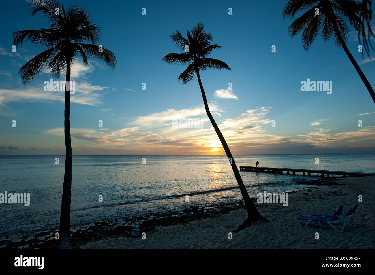 Sunset with palm trees and couple, Bayahibe Beach, Dominican Republic - Stock Image