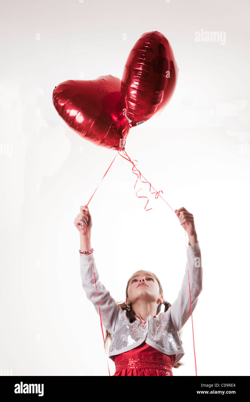happy girl holding a heart shaped balloon - Stock Image