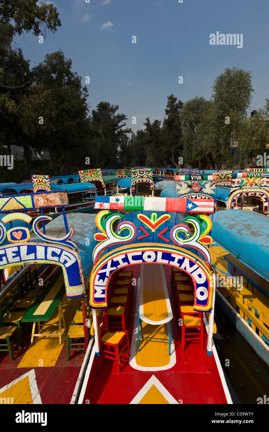 """Colorful canal boats or trajineras await tourists at Xochimilco or """"the floating gardens"""" in southern Mexico City. Stock Photo"""