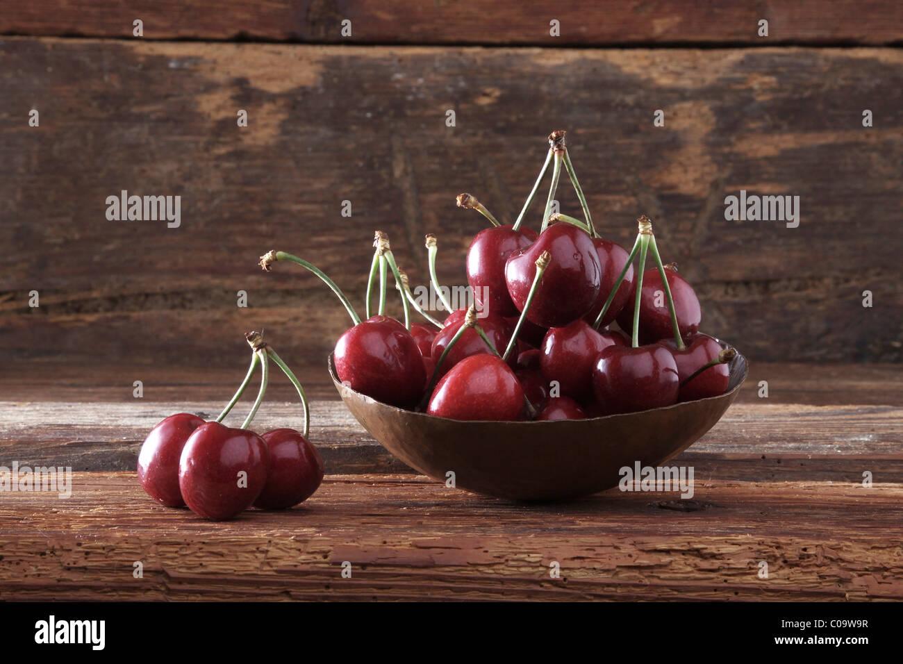 Bowl of Cherries (Prunus) in front of rustic wood - Stock Image