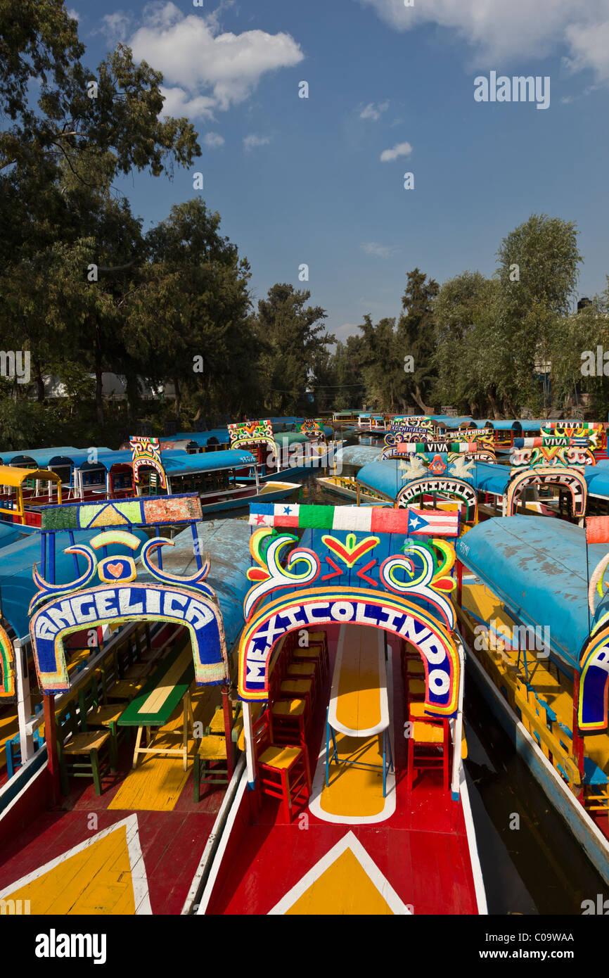 Colorful canal boats or trajineras await tourists at Xochimilco or 'the floating gardens' in southern Mexico - Stock Image