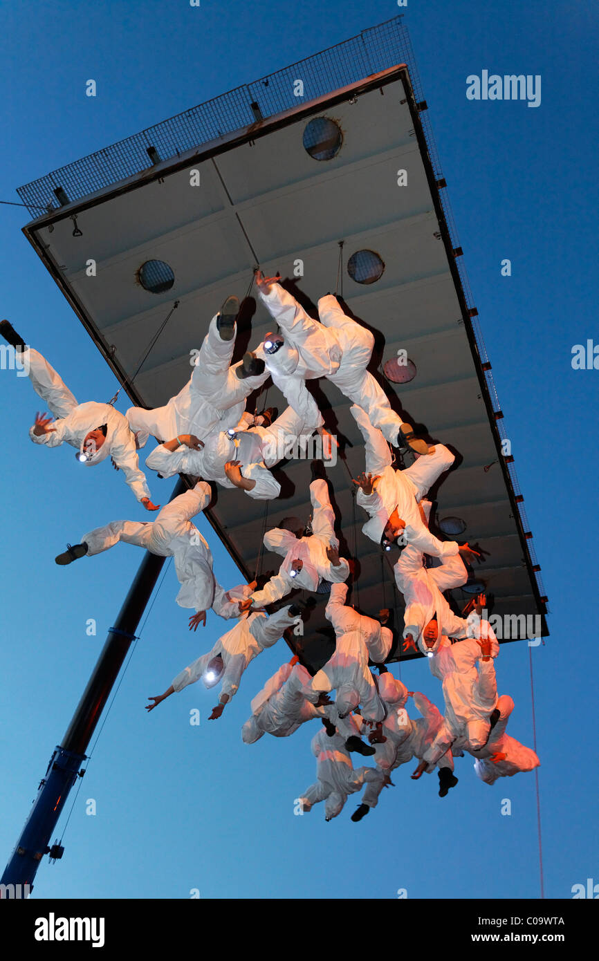 White-clad trapeze artists hanging upside down from a platform in the air, Global Rheingold, open-air theater by - Stock Image