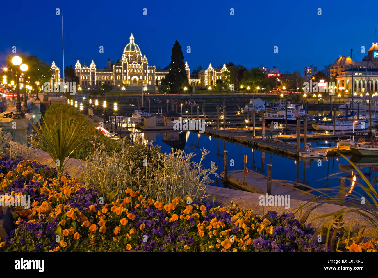 Victoria's Inner Harbour illuminated at twilight with the BC parliament buildings in the background, Victoria, - Stock Image