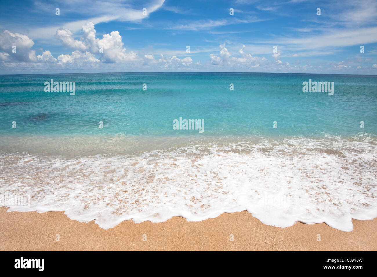 Empty beach with white wave spray - Stock Image