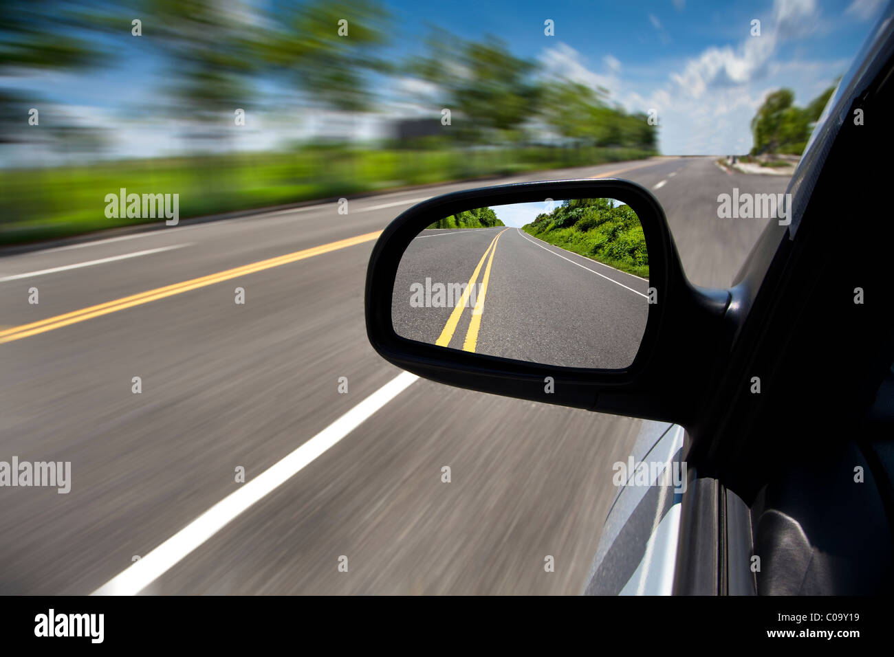 car driving through the empty road and focus on mirror - Stock Image