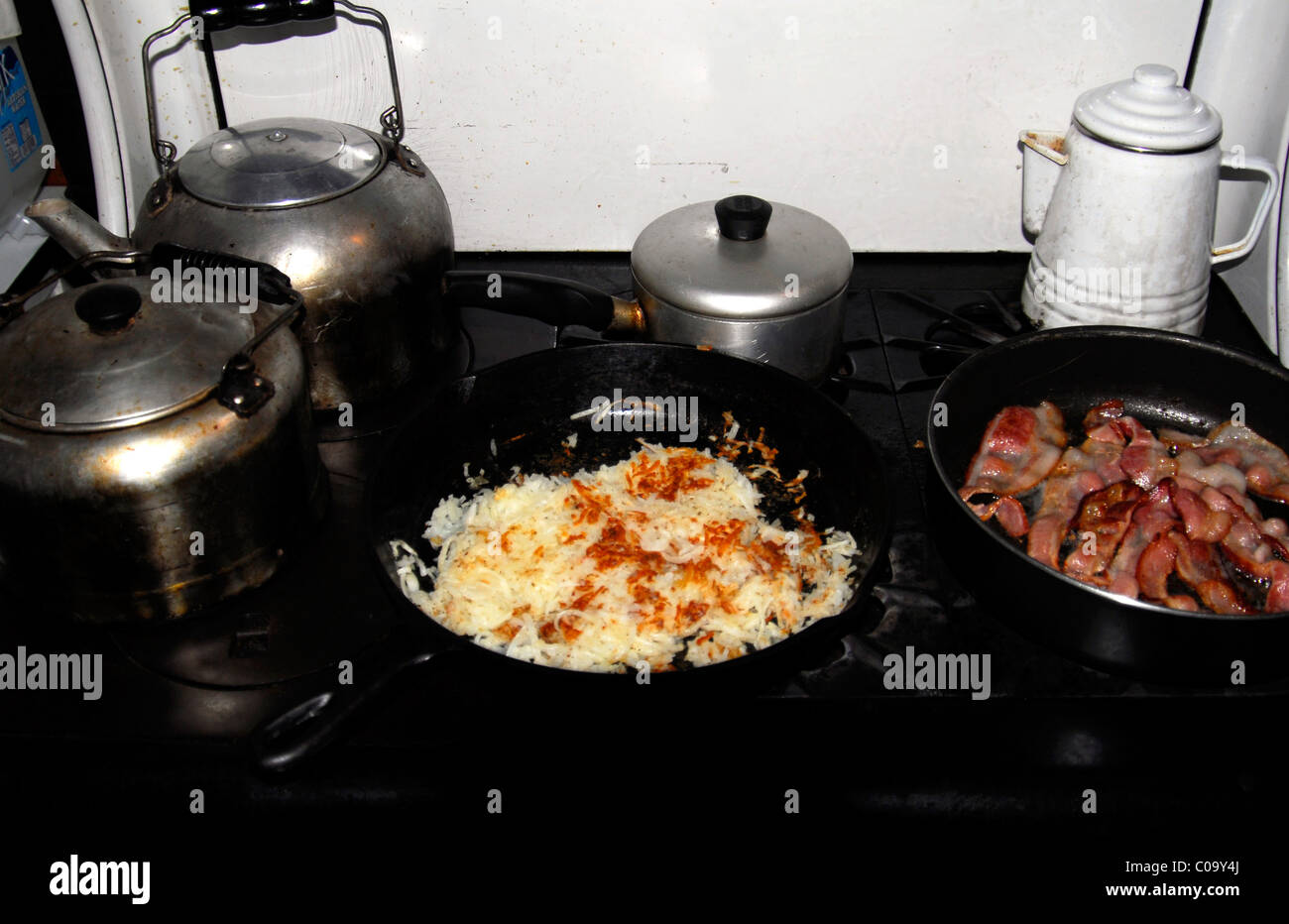 Breakfast food cooking on an antique old cabin stove - Stock Image