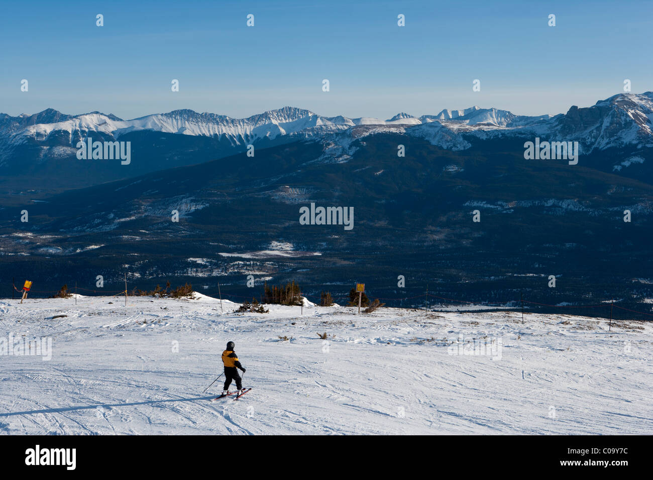 Single Skier overlooking mountain vista from on piste ski area. Rockey Mountains Alberta, Canada. - Stock Image