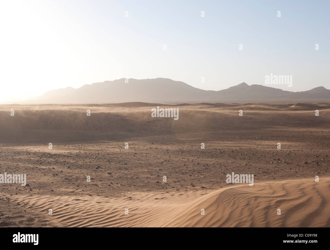 Sand dunes (Ergs) in Sahara desert caused by  aeolian processes with mountain terrain in distance. Morocco. - Stock Image