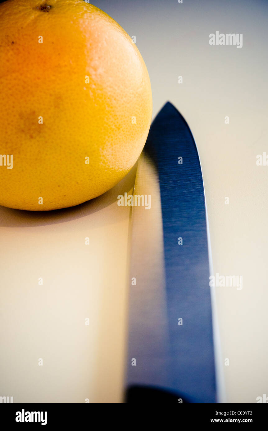 Orange with knife beside it - Stock Image