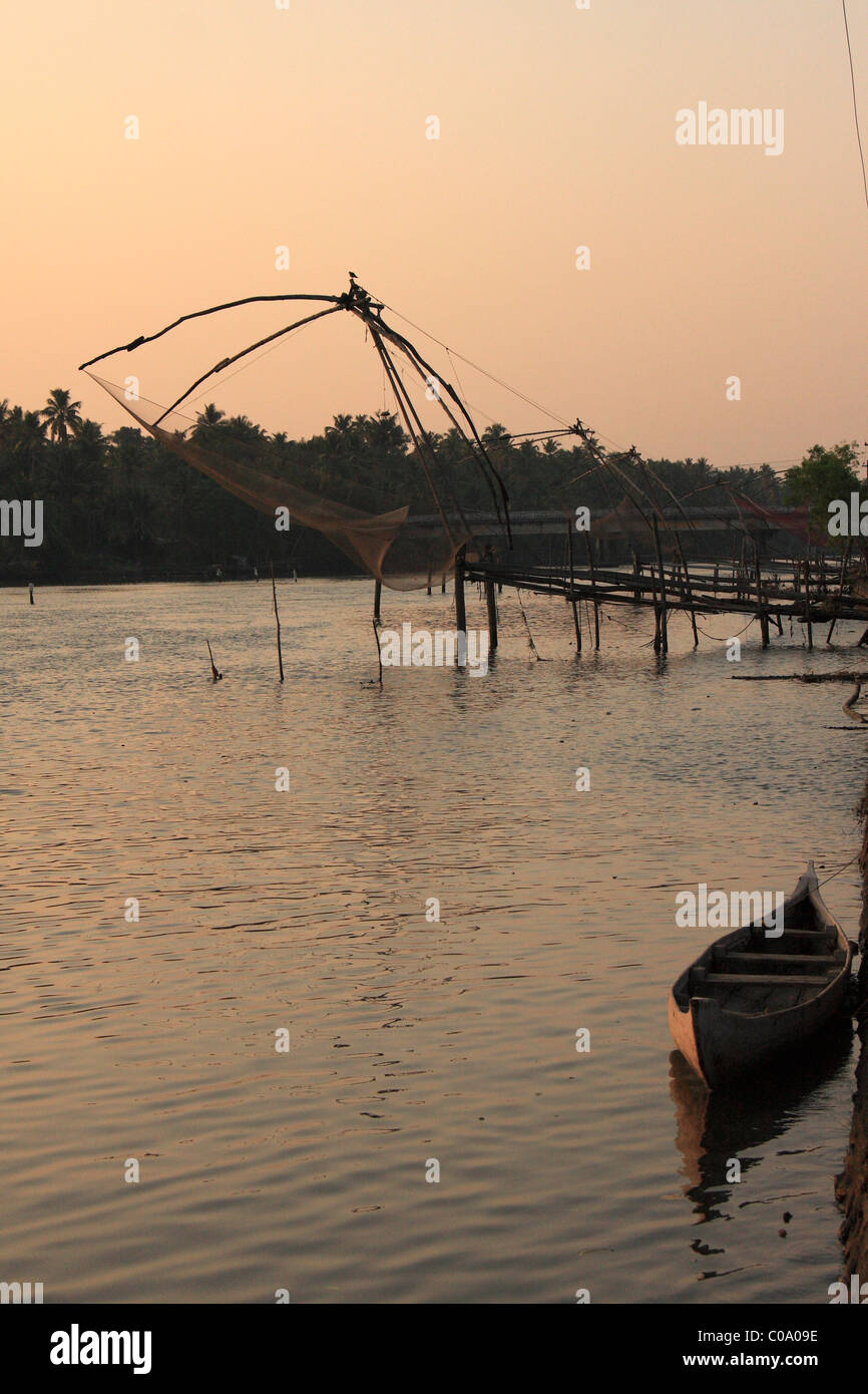 wooen boat and chinese fish nets in sunset, kerala,india - Stock Image