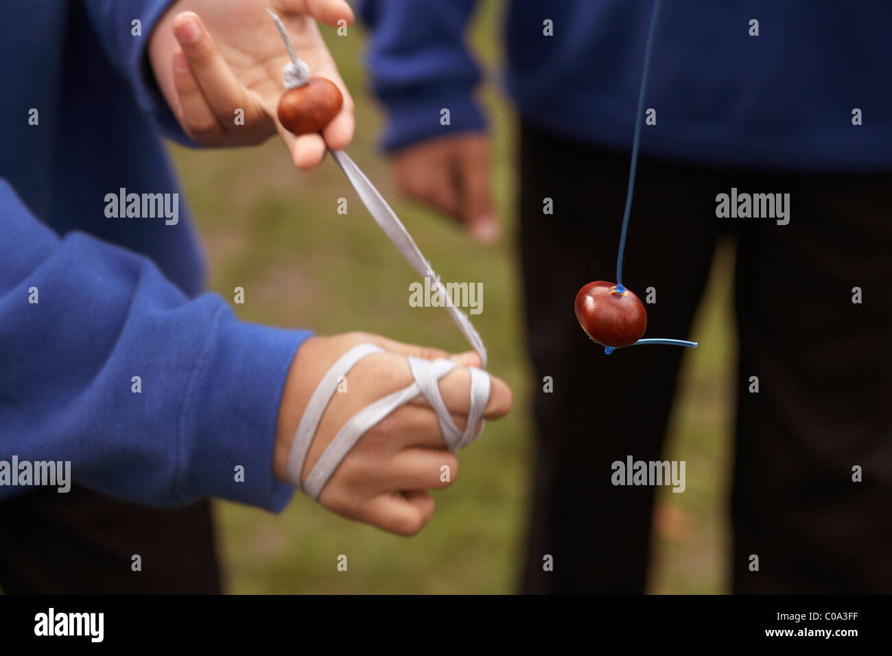 Children playing a game of conkers in the playground at school wearing blue school uniforms - Stock Image
