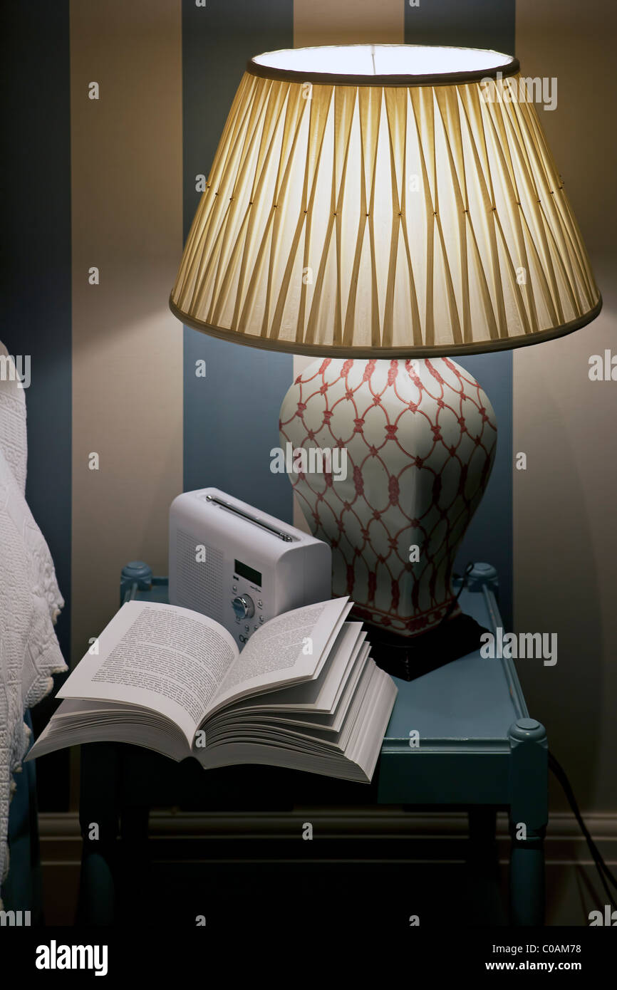 Bedside table with lamp, radio and open book - Stock Image