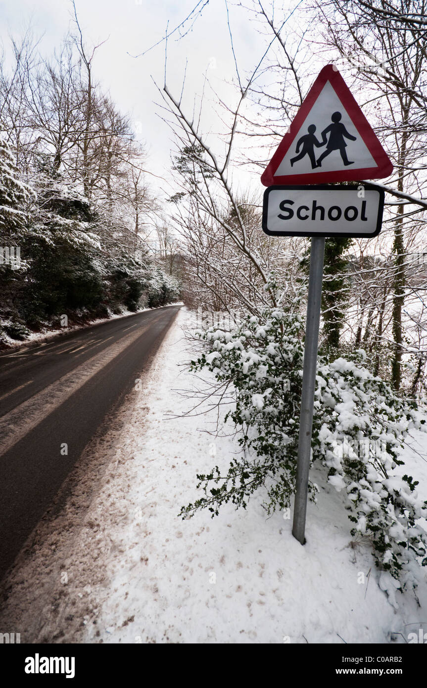 School roadsign on a snowy country lane UK - Stock Image