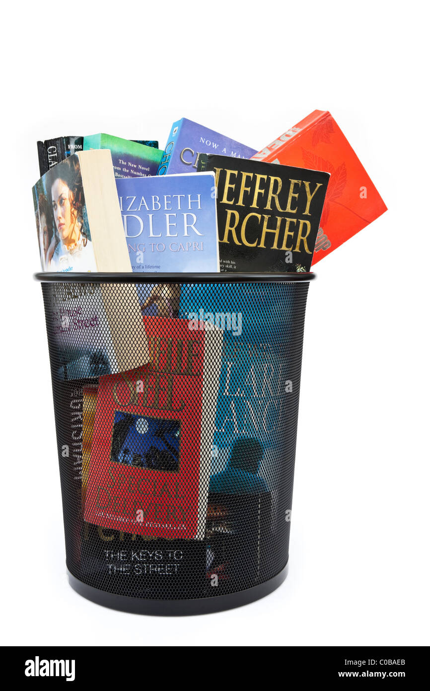 Paperback books thrown away in a wastepaper bin to illustrate changing reading habits concept. England UK Britain - Stock Image