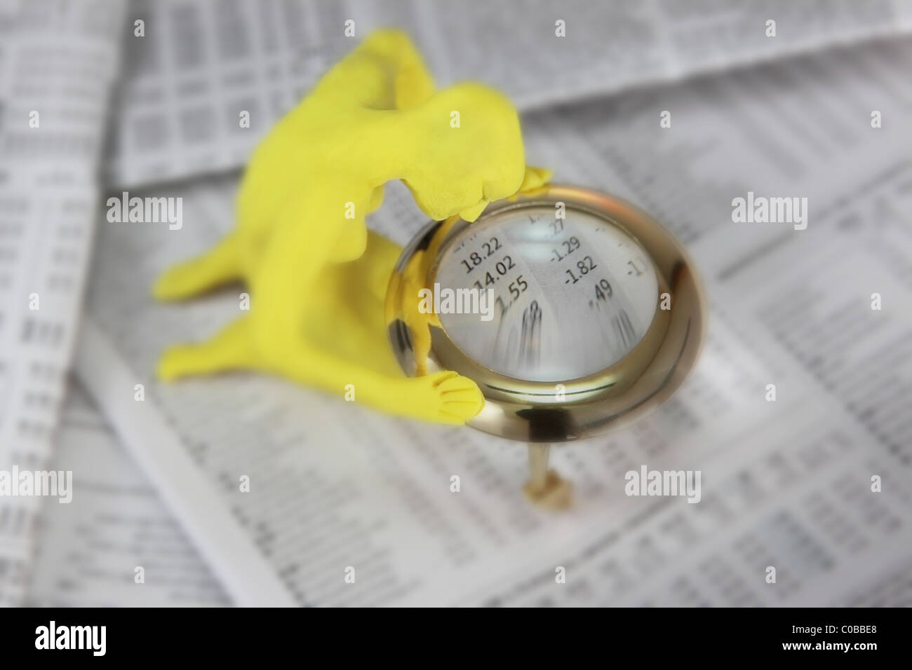 yellow plasticine figurine looking through magnifying glass at newspaper stock markets - Stock Image