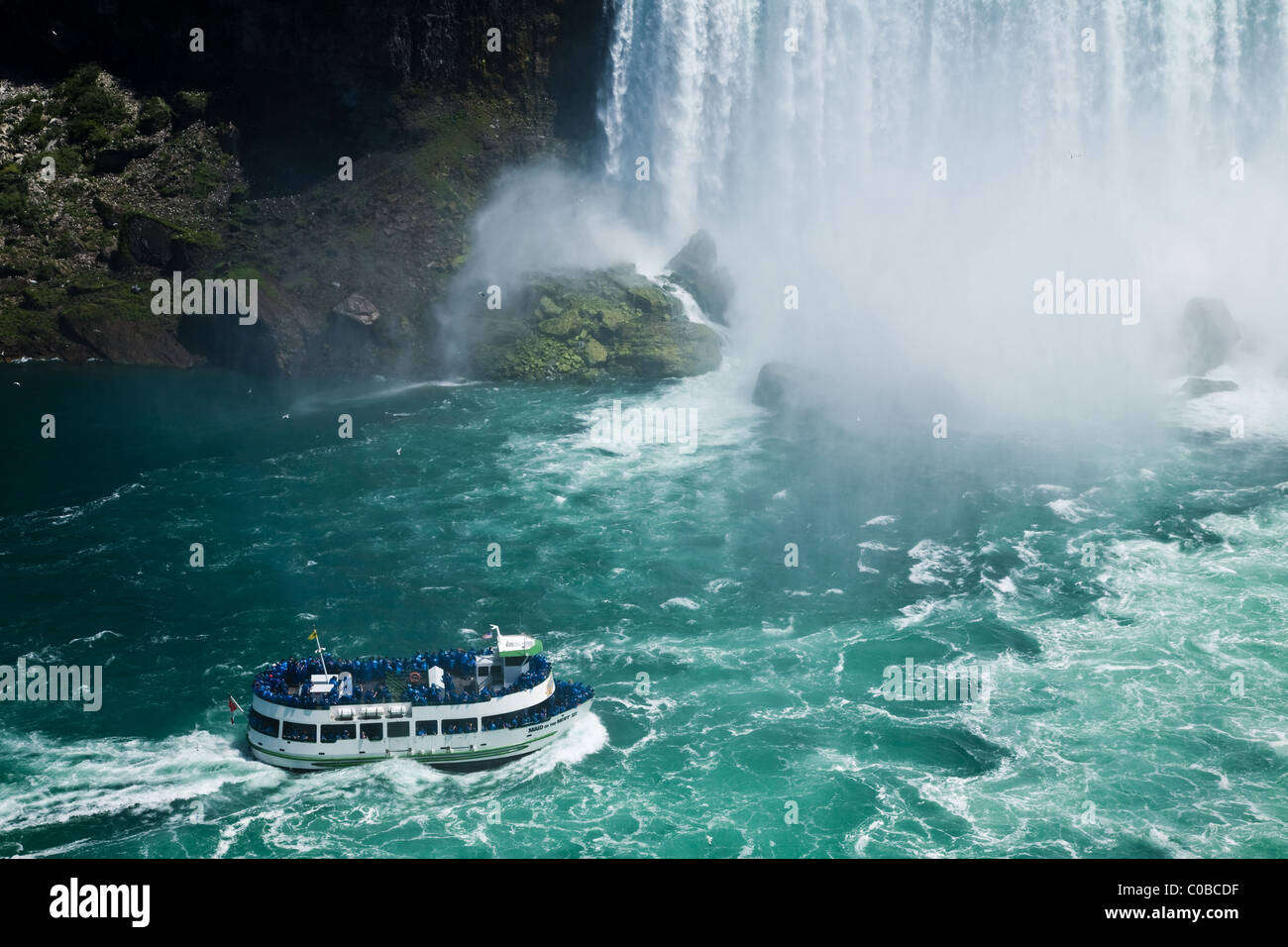 Tour boat with visitors at the base of Niagara falls - Stock Image